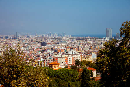 Panoramic view of sunny Barcelona in Spain. Roofs of the houses and blue sea. High quality photo Imagens