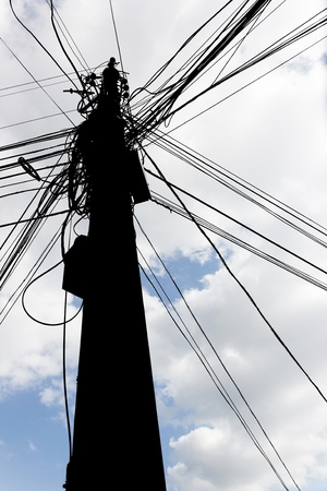 black isolated chaotic mess of a wires on a pillar on cloudy sky background Stock Photo - 10627402
