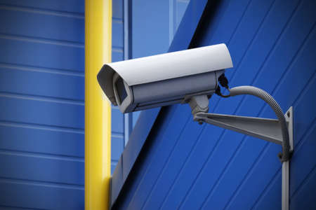 security camera: surveillance camera on blue wall next to yellow pipe Stock Photo