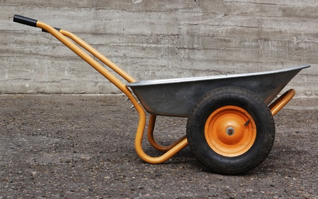 orange two weel farmers wheelbarrow on concrete background