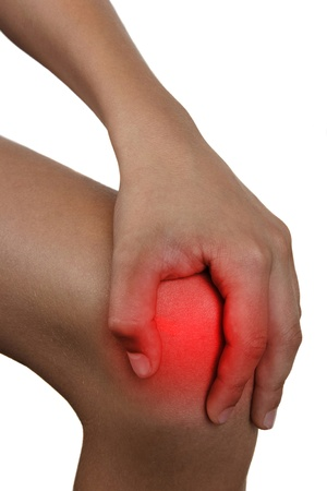young boy one palm over knee cap to show pain and injury on knee area. Stock Photo