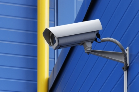 surveillance camera on blue wall next to yellow pipe Stock Photo