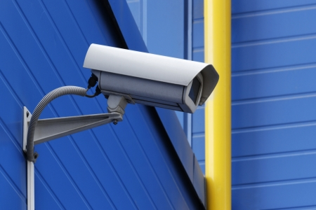surveillance camera on blue wall next to yellow pipe photo