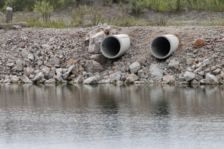 pollution water: two dry pipes on waterside pointed to the river