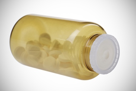 strew: Closed brown jar with pills  isolated on white background