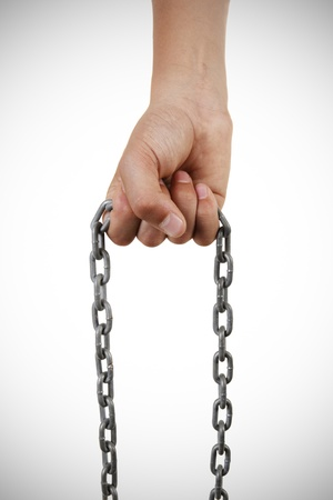 submissiveness: young boys hand holding a chain. isolated on white background