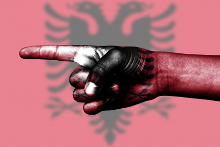 human hand point with finger in albanian national flag
