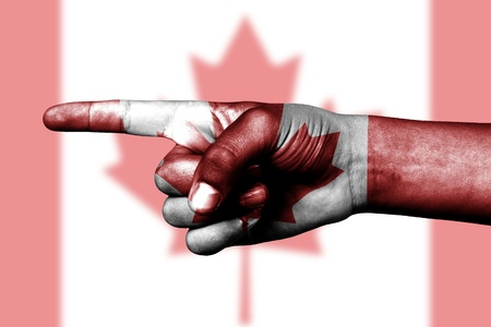 Human hand point with finger in Canada national flag