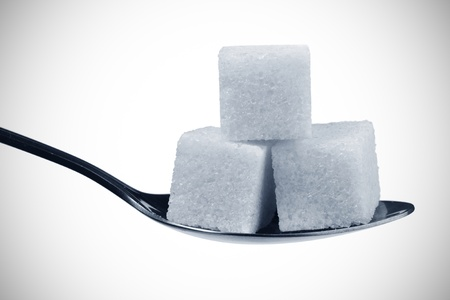 sugar cubes: Spoon with sugar cubes isolated on a white background
