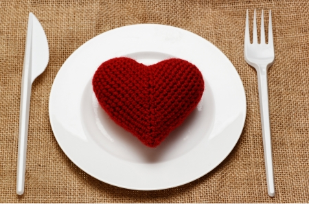 clean arteries: red heart in white plate with plastic knife and fork Stock Photo