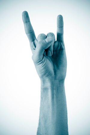 A mans hand giving the Rock and Roll sign isolated on a white background Stock Photo