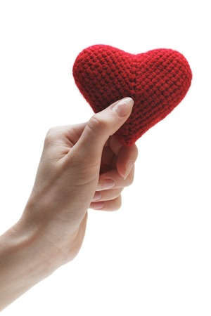 solicitude: Handmade red heart in a womans hand. Isolated on white background Stock Photo