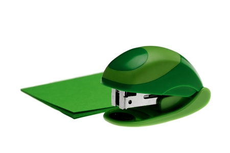 office stapler: Small green stapler next to green paper. Isolated on white Stock Photo