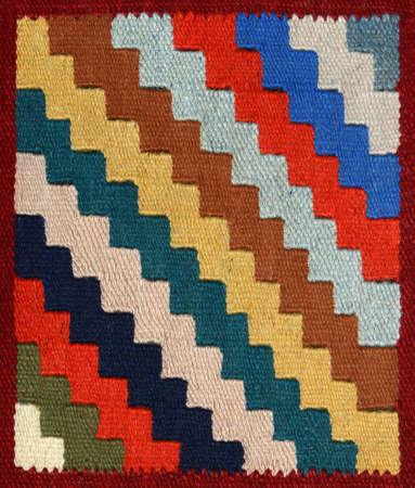 깔개: Closeup of decorative carpet fabric pattern with multi-colour bright geometrical ornament in the form of zigzag diagonal strips