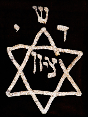 Antique decorative star of David and hebrew letters made from textured fabric on old dark fabric background.Jerusalem flea market. Stock Photo