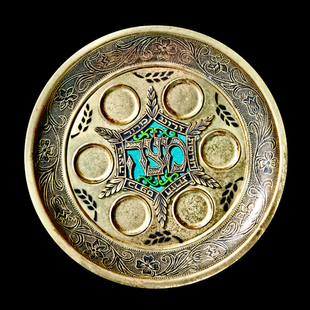 Antique decorative metallic traditional passover seder plate.   Isolated on black background.Jerusalem flea market.