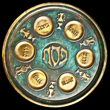 Antique decorative metallic traditional passover seder plate.   Isolated on dark background.Jerusalem flea market