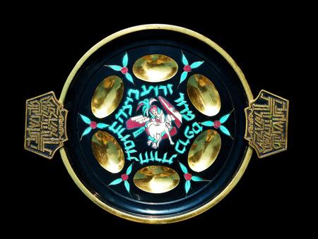 hebrew letters: Antique decorative metallic traditional passover seder plate.   Isolated on black background.Jerusalem flea market.