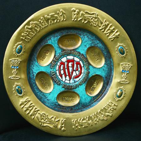 Antique decorative metallic traditional passover seder plate.   Isolated on dark background.Jerusalem flea market.
