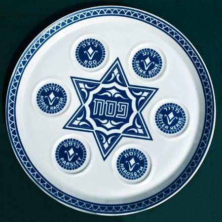 Antique traditional decorative plate for passover seder. Blue star of David and 6 blue circles on white ceramic dish. Isolated on dark background.Jerusalem flea market.   Stock Photo