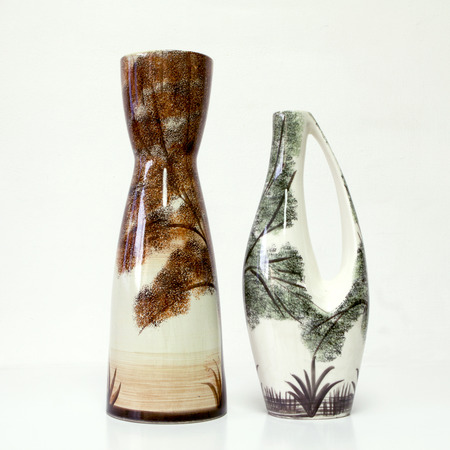 American ceramic pair in white brown and green tones: two vases of 1950-th years. Unusual forms, glazed surfaces, floral drawing. Symbolizes couple: He and She; Brother and sister, bride and groom etc. Isolated on white.