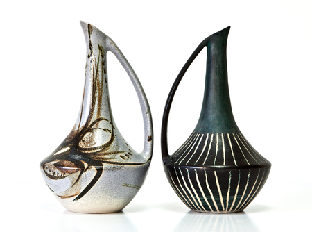 Israeli ceramic pair in black gray and brown tones: two vases of 1950-th years. Unusual forms, glazed surfaces, abstract drawing. Symbolizes couple: He and She; Brother and sister, bride and groom etc. Isolated on white. Stock Photo