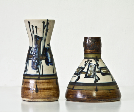 Israeli ceramic pair in bright blue and brown tones: two vases of 1950-th years. Contrast forms, abstract images.Symbolizes couple: He and She; Brother and sister etc. Isolated on white.