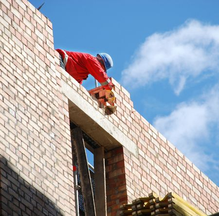 mason: The mason behind work. House building. Stock Photo