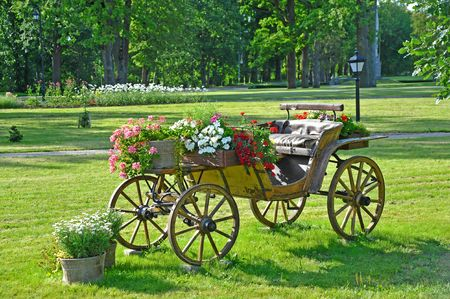 Ancient cart decorated with flowers in landscape park