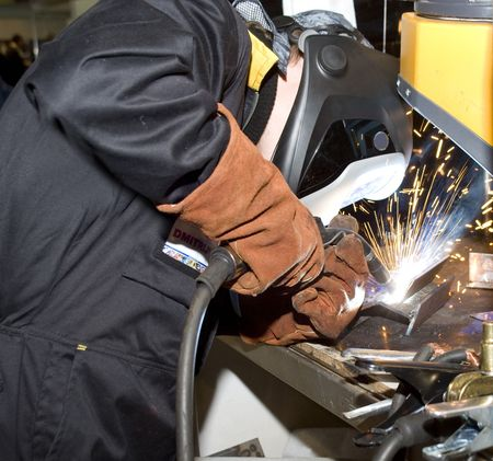 The welder in protective clothes behind job photo