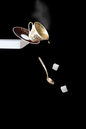 Trouble! Falling of a cup of coffee from a table.
