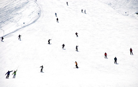 Mass descent of mountain skiers from a wide hillside Stock Photo