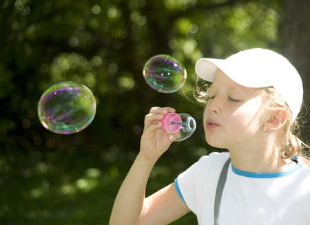 amuse: The girl amuse oneself, starting up multi-colored soap bubbles