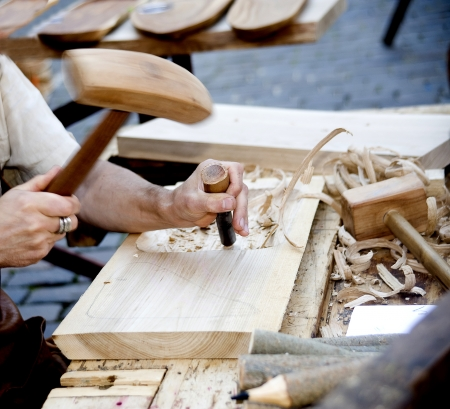 The joiner does a dimple in a board, working with a chisel  photo