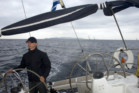 The captain controls the yacht on a regatta in the Aegean Sea.