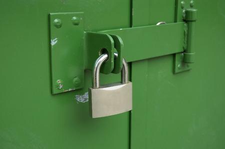 green door: The hinged mechanical lock on doors of garage Stock Photo