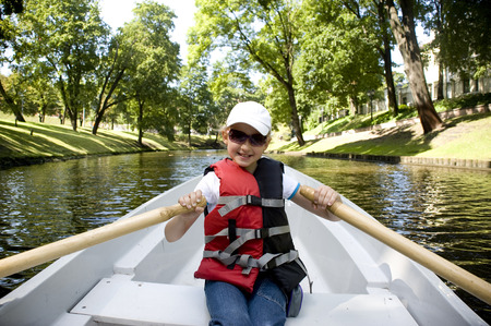 The girl in the boat on oars on the channel in Riga Stock Photo