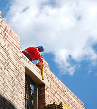 Mason checks the level of quality of masonry brick in the construction of houses