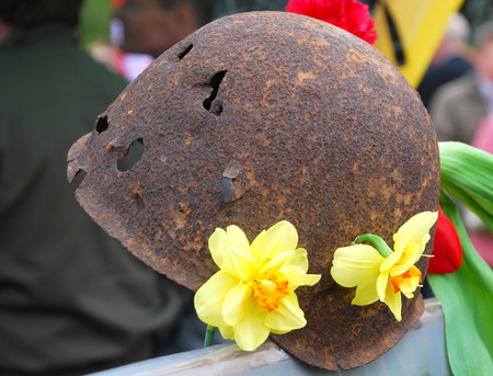 Memory of the Victory! The soldiers helmet punched by bullets decorated with flowers.