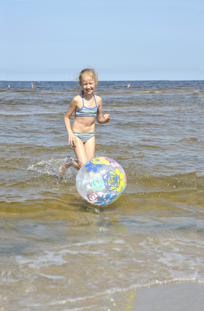 jurmala: The girl plays with a ball at seacoast in Jurmala Latvia. Stock Photo