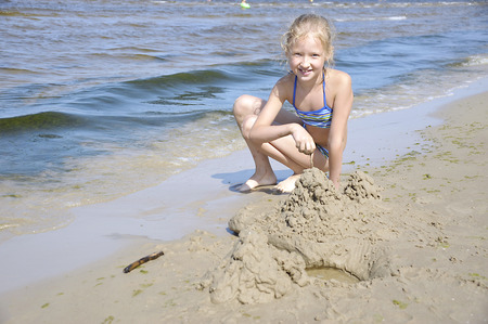 jurmala: Baltic, Latvia, Jurmala. Girl playing with sand on the beach. Stock Photo