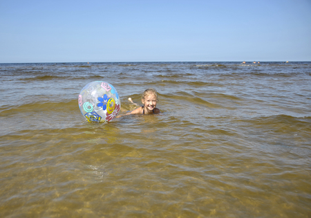 latvia girls: Baltic, Latvia, Jurmala. The girl with a ball swims in the sea.