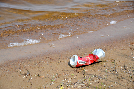 can: Metal, crumpled bank from drink it is thrown out on the bank of a reservoir Stock Photo