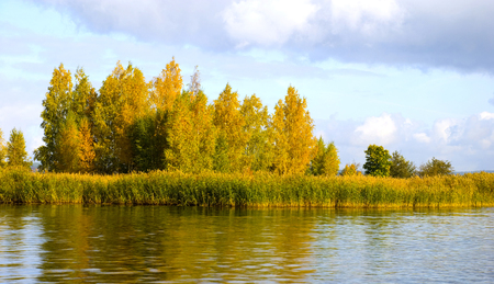 Autumn landscape. The island on the lake with trees in beautiful autumn foliage.
