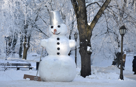 Big snowman in the park in December before Christmas Stock Photo