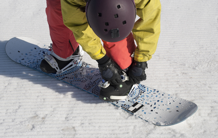 The athlete checks fastenings before descent from the mountain on a snowboard. Stock Photo