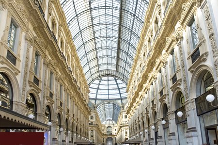 Italy, Milan. Vittorios galleries of Emmanuel II. The building of a passage with a glass roof has a form of a Latin cross with the octagonal center decorated with mosaics. The Milan trade gallery connects the square in front of a city cathedral to the sq Editorial