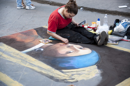 Florence, Italy - may 17.2015: The young girl,  the artist  draws the copy of a portrait on the sidewalk. Editorial
