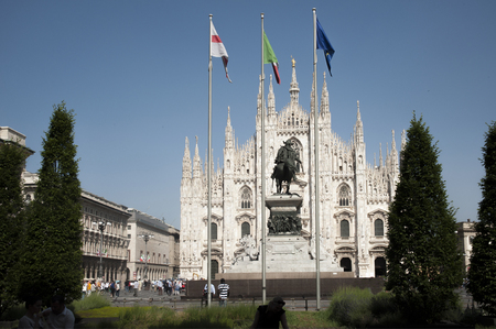 Milan, Italy - May 14,2015:  Piazza del Duomo, the cathedral of Santa Maria Nashente (Duomo) - the symbol of Milan - the pearl of the Italian Gothic. Equestrian Statue Emmanuel II the first king of united Italy new time.