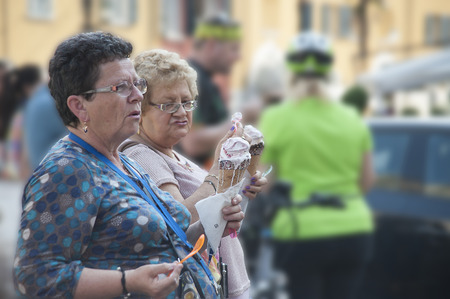 Garda, Itali - May 18,2015: Two corpulent ladies talk, holding huge portions of the ice cream corresponding to their proportions in hand. Editorial